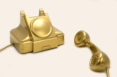The gold telephone. The telephone of gold colour on a white background Royalty Free Stock Photo