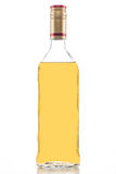 Gold tequila bottle. Isolated gold tequila bottle, clear tall alcohol bottle full of yellow liquid on a white background Royalty Free Stock Photography