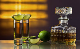Gold tequila. And lime on a glass table Stock Image