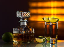 Gold tequila. And lime on a glass table Stock Photo