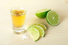 Gold Tequila with lime slices and salt Stock Images