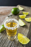 Gold tequila shot with lime slices on rustic wooden table Royalty Free Stock Photography