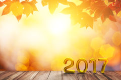 Gold 2017 Text on old wood on red maple in autumn and bokeh light background. For Happy New Year Concept Royalty Free Stock Photo