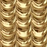 Gold textile fabric drapery material seamless pattern texture background with a metallic reflection Stock Image