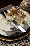 Gold theme Christmas dinner table setting. Close up on cutlery and plates Stock Photography