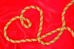 Gold thread on red satin Stock Images