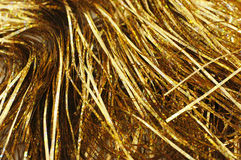Gold tinsel. Closeup of gold Christmas tinsel strewn on table Stock Images