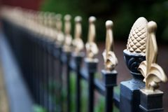Gold tipped Iron fence narrow DOF. Very narrow dept of field focus on the pineapple post with gold tiped spikes diminishing to very soft focus royalty free stock image