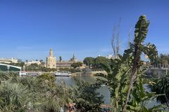 The Gold Tower next to the Guadalquivir River in the city of Seville, Spain. Typical postcard of the Guadalquivir river next to the tower of gold in the city of royalty free stock photo