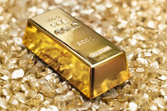 Gold treasure. Gold bullion on gold nuggets Royalty Free Stock Images