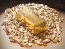 Gold treasure. Gold bullion on gold nuggets Royalty Free Stock Photos