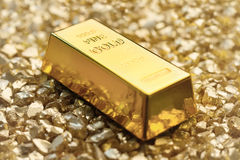 Gold treasure. Gold bullion on gold nuggets Stock Images