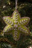 Gold Trimmed Green Star Christmas Ornament on Fir Tree. Portrait shot of a green star with silver appliqué hangs on a Christmas fir tree stock photography