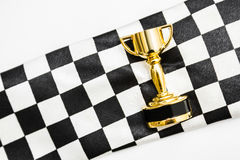 Gold trophy on a checked sport flag Royalty Free Stock Photos