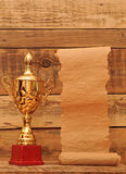 Gold trophy cup. With blank old paper scroll over wooden background stock images