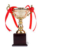Gold trophy with red decorative ribbons on wooden table Stock Image