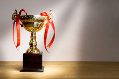 Gold trophy with red decorative ribbons on wooden table. Elegant gold trophy with red decorative ribbons on wooden table with ray of light. Fine art rendition royalty free stock photos
