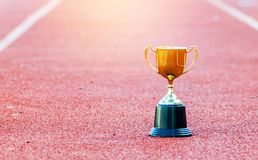 Gold trophy on red Track in stadium. Leadership ;success in business concept stock image