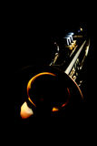 Gold trumpet. Gold lacquer trumpet with mouthpiece in the dark Royalty Free Stock Images
