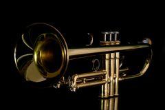 Gold trumpet in night. Gold lacquer trumpet with mouthpiece isolated on black Stock Images
