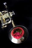 Gold Trumpet with a Red Rose. A gold brass trumpet and red rose against a black background in vertical format with copy space Stock Photos