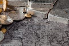 Gold-u. Silbermünzen u. Stangen auf Karte über Europa, Asien, Afrika Lizenzfreie Stockbilder