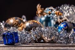 Gold und blauer Weihnachtsball mit kleinem blauem Geschenk auf schwarzem Hintergrund lizenzfreie stockbilder