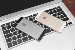 Gold- und Raumgrau IPhones 5s auf silbernem Laptop Stockfotos