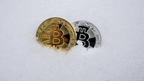 Gold- und Silber bitcoin Cryptocurrency auf Schnee, im Hintergrund Das Konzept des Freiberuflich tätig seins, die Börse gold Lizenzfreie Stockfotografie