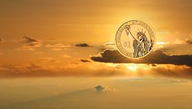 Gold US dollar on sunrise sky. Business success. Abstract of the business, financial success.The gold shining Us dollar is rising on the beautiful background of stock photo