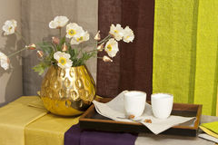 Gold vase. With flowers and two coffee cups on a tray royalty free stock photos