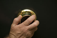 Gold vault Combination dial. Close up of a hand turning the dial on dark colored vault door Royalty Free Stock Photos
