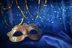 gold venetian mask on blue silk background Stock Photo
