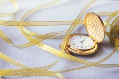 Gold Vintage pocket watch with golden ribbons on grey cement background. Hourglass or sand timer, symbol of time. Selective focus royalty free stock photo