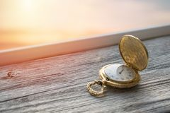 Gold Vintage pocket watch with sunset light on wooden background. Hourglass or sand timer, symbol of time. Selective focus stock photo