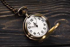Gold vintage pocket watch. On a wooden table. Old time background Stock Photography