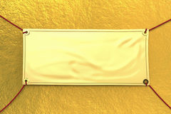 Gold vinyl banner. Hanging with red rope stock photography