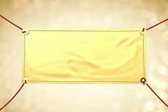 Gold vinyl banner. Hanging with red rope stock image