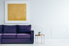 Gold and violet living room. Copper table next to violet settee against grey wall with gold painting in living room interior Royalty Free Stock Photo