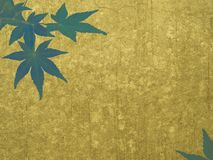 Gold wall with green maple leaves Royalty Free Stock Photos