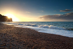 Gold warm sunset over ocean waves stock photo