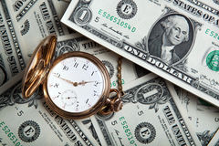 Gold watch and dollar bills Stock Images