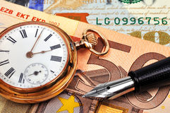 Gold watch and euro bills Stock Images