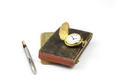 Gold Watch and Pen with old books. A view of a gold watch and a silver pen on a old book Royalty Free Stock Photography