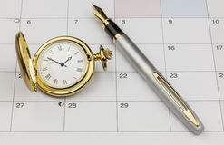 Gold Watch and Pen. A view of a gold watch and a silver pen on a monthly calendar Stock Photos