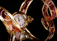 Gold watch and a red delicate ribbon on a black Royalty Free Stock Photography