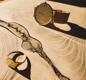 Gold watch and signet on wooden background royalty free stock image