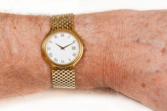 Gold watch with white face on hairy wrist. Gold watch and band in close up on wrist of hairy senior man Stock Photo