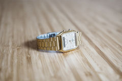 Gold watch on wood Stock Image