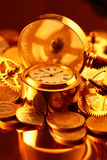 Gold watches, coins, gears and magnifying glass. On the mirror surface Royalty Free Stock Images
